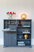 Dark grey sideboard with fold-down reading desk and ornaments in shelf compartments