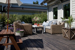 Picnic table and wicker sofas on sunny terrace adjoining house