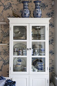 Blue-and-white crockery in classic display case against floral wallpaper