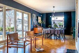 Klassikerstühle und Essbereich in offenem Wohnraum mit blauen Wänden