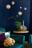 Petrolfarbener Polstersessel im Wohnraum mit blauen Wänden