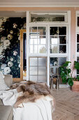 Wall made from windows separating hallway with rose-patterned wallpaper