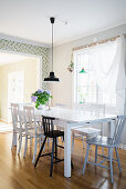 Black pendant lamp and vase of flowers in dining area