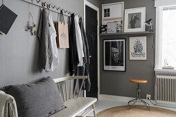 Hakenleiste über einer Sprossenbank im Schlafzimmer in Grau