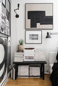 Magazines stacked on bench in black-and-white living room