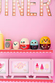 Retro figurines and picture frames on shelves on pink wall