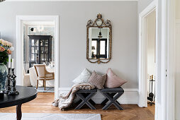 Cushions on upholstered stools below antique mirror on wall and view into dining room