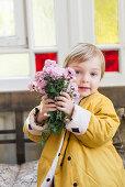 Junge in gelber Jacke mit Blumenstrauß