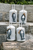 Hand-sewn denim fish ornaments with silver skeletons