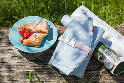 Pastries and strawberries on plate, hand-sewn picnic bag and magazine