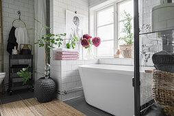White, modern bathtub in tiled niche below bathroom window