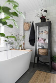 Black display case next to modern, free-standing bathtub