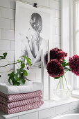 Towels, candles and flowers on tiled shelf in bathroom