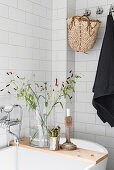 Candlestick and vase of grasses on wooden bath caddy