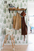 Chopping boards and leather apron hung from coat rack and baby's high chair in hallway with botanical wallpaper
