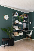 String shelves with desk top and houseplants in room with green walls