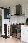Large cooker with oven, firewood store and wood-burning stove in kitchen with white wall tiles