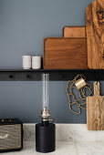 Wooden boards and trays on black ledge, oil lamp on marble worksurface and blue-grey wall in kitchen