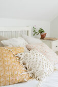 Collection of scatter cushions on double bed in bedroom