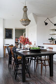Black dining table and wooden chairs below vintage chandelier in dining area
