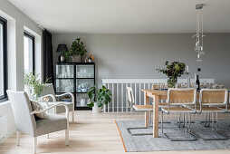 Black cabinet, pale wooden dining table and cane chairs in interior with pale grey walls