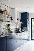 Contemporary kitchen with blue cabinets and white-tiled wall