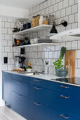 Kitchen with blue cupboards and white tiled wall