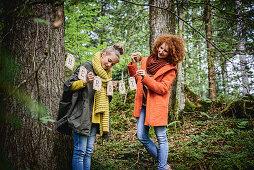 Mädchen und Frau hängen Herbstgirlande im Wald auf