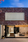Modern brick house with window front to the open living room