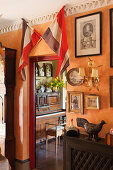 Two French flags above doorway leading into room with piano