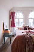 Scatter cushions and bedspread on double bed in front of arched bedroom windows