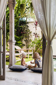 Two children are sitting with cushions on the terrace in the exotic garden