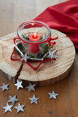 Candle in jar on wooden board in rustic star made from nails and felt yarn