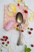 Spoon, cake fork and wild strawberries