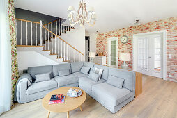 Grey sofa in open-plan interior with staircase and brick wall