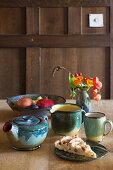 Keramikgefäße, Apfelkuchen und Herbststräusschen auf Holztisch