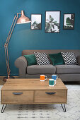Living room with grey sofa, coffee table and petrol-blue wall