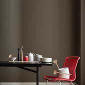 Crockery on black table and red chair in front of dark wall