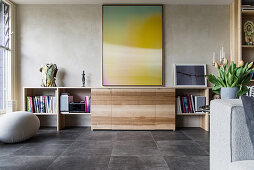 Large artwork above sideboard in open-plan living room with tiled floor
