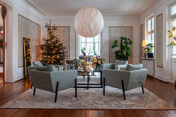 Christmas tree and blue armchairs in elegant living room