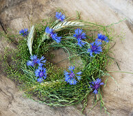 Cornflower and rye ear wreath with grass and straw