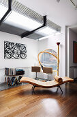 Curved lounge chair in the corner of the room next to a round swing window