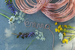 Name formed from copper wire above wild summer flowers