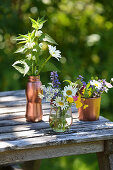 Wildflower posies in glass vase and copper-coloured containers