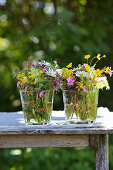 Wildflower posies in glass vases decorated with paint pens