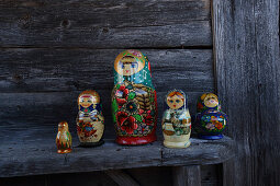 Traditional Russian dolls on wooden bench outside cabin