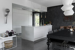White island counter and black dining table in modern, open-plan kitchen