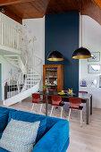 Blue velvet sofa, table in dining area and antique dresser in maisonette apartment