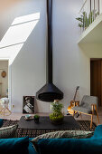 Suspended fireplace with double-height stove pipe in maisonette apartment