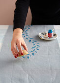Printing a pattern on a tablecloth runner using a potato stamp